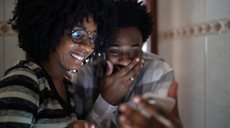 Como ganhar no jogo do bicho: Casal recebendo notícias surpreendentes no celular em casa
