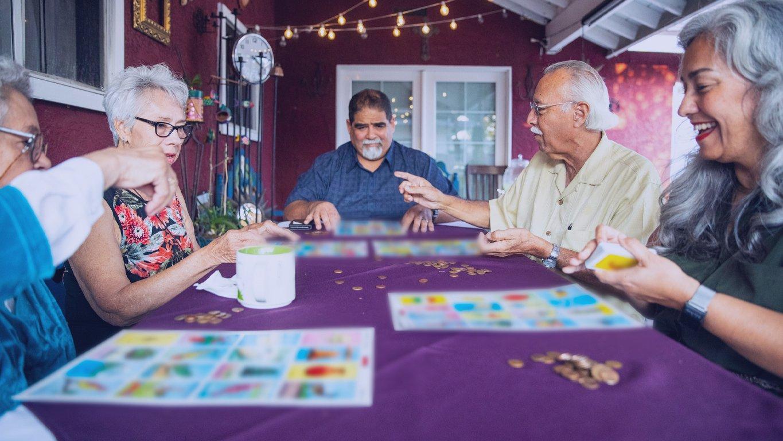 pessoas jogando bingo em uma varanda externa de uma casa