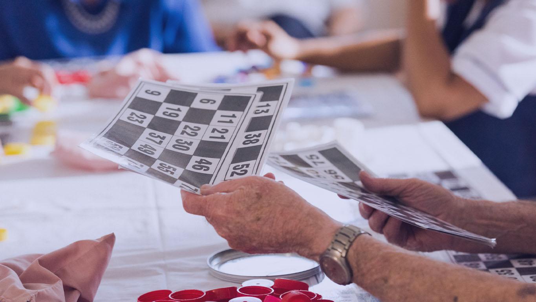 mãos do homem sênior distribuindo cartões numéricos para um jogo de bingo