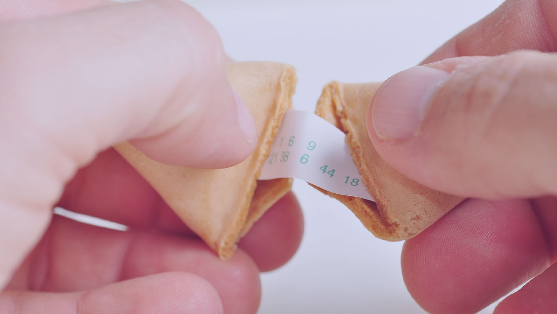 mãos abrindo biscoito da sorte