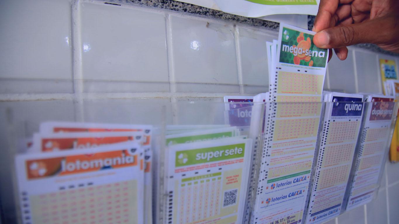 Escolher as dezenas da loteria: Pessoa retirando um bilhete de mega sena na lotérica