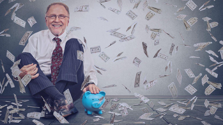 Homem sênior feliz animado sentado no chão com o cofrinho sob uma chuva de dinheiro, isolada no fundo da parede cinza. Emoções positivas, sucesso financeiro, sorte, boa economia, conceito