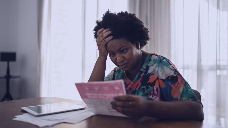 Mulher preocupada procurando contas financeiras em casa