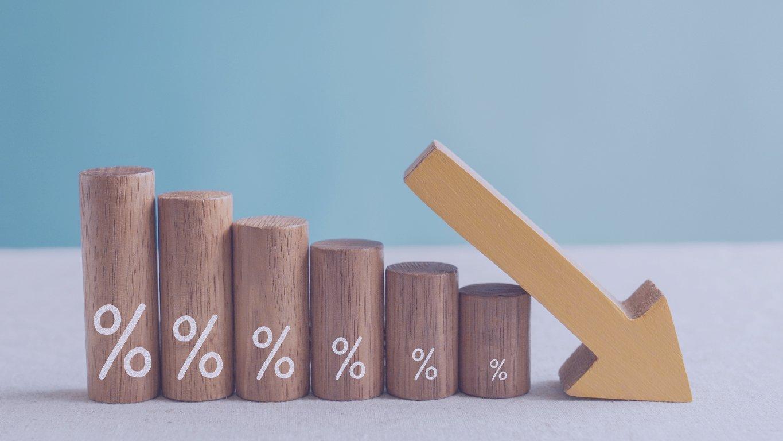 Blocos de madeira com sinal de porcentagem e seta para baixo, crise de recessão financeira, queda da taxa de juros, conceito de gestão de risco