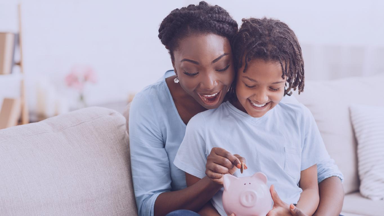 Poupar dinheiro mensalmente: Conceito de economia de dinheiro. Mãe e filha negras animadas colocando moedas no cofrinho, espaço livre
