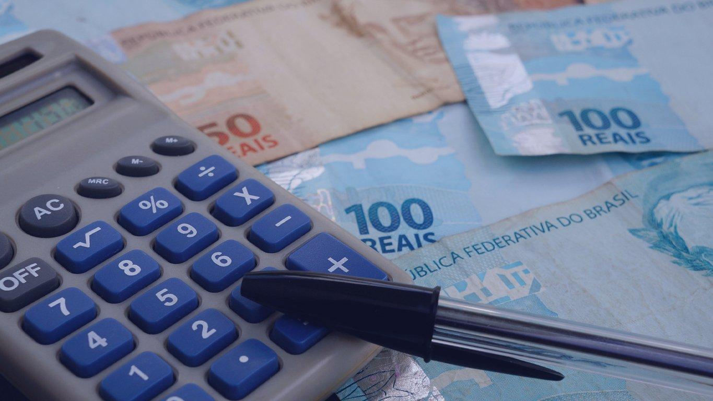 Conceito de finanças - calculadora, dinheiro brasileiro e caneta em fundo preto.