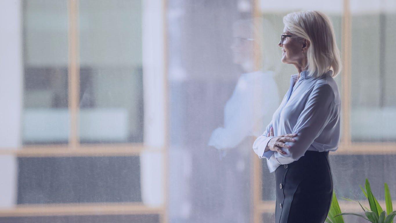 Veja como funciona a aposentadoria no Brasil: Sorrindo, empresária madura confiante ponderando sobre a estratégia, perto de uma grande janela em um escritório moderno, olhando a paisagem urbana, empresário perdido em pensamentos, planejando projeto futuro, visão de negócios