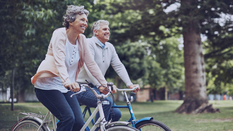 Foto recortada de um casal maduro curtindo um passeio de bicicleta no parque